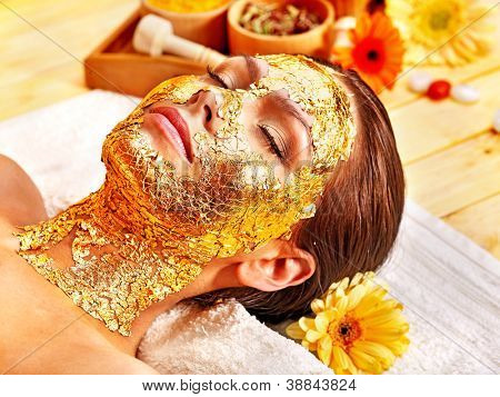 Woman getting  gold facial mask. poster