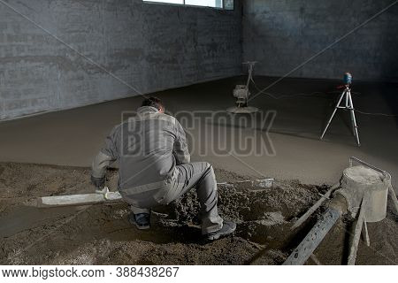 Filling The Floor With Concrete, Screed And Leveling The Floor By Construction Workers. Smooth Floor