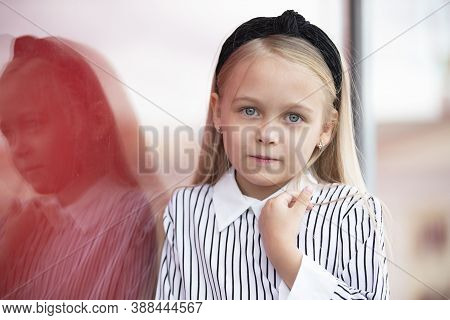 Beautiful Little Blonde Girl With A Reflection In The Glass. Portrait Of A Girl Of Elementary Age.