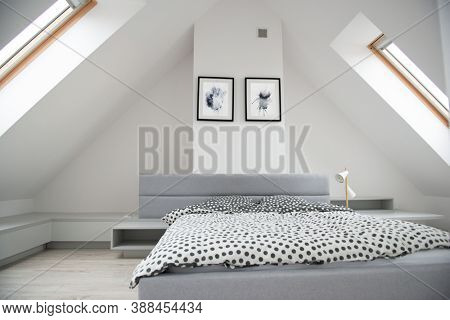 Modern monochrome design home interior of bedroom room in mansard with wooden bed and elegant accessories. Stylish home decor with mock up abstract paintings on the wall.