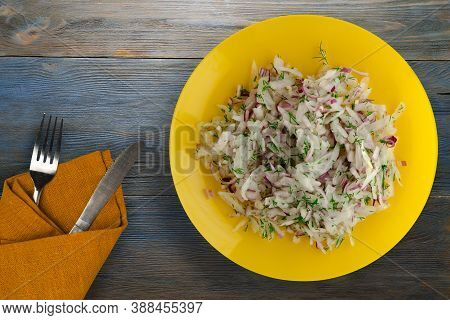 Salad Daikon, Onions And Dill On Blue Grey Wooden Background. Salad On Yellow Plate With Fork And Kn