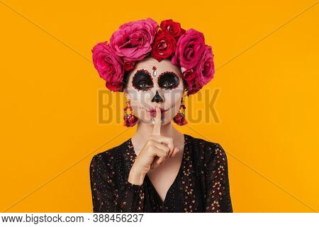 Beautiful woman in halloween makeup and flower wreath making silence gesture isolated over yellow wall