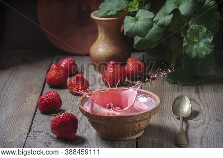Milk Dessert With Strawberries In A Ceramic Bowl On A Wooden Background. Falling Strawberries And Sp