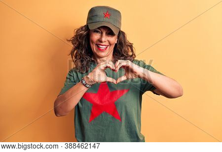 Middle age brunette woman wearing t-shirt and cap with red star symbol of communism smiling in love doing heart symbol shape with hands. Romantic concept.