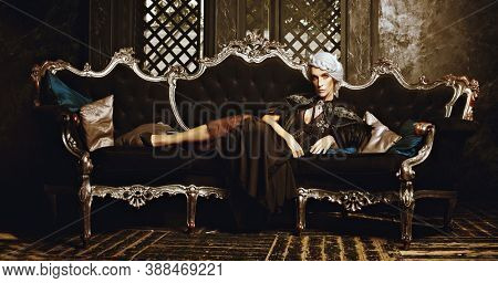 A beautiful old woman, a noble widow with gray hair and a rich black dress, lies on a vintage sofa in her old castle. Black widow. Fantasy world. Halloween.
