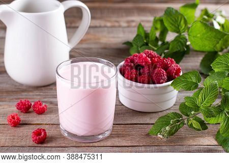 Homemade Yoghurt In A Glass Glass With Organic Raspberries.