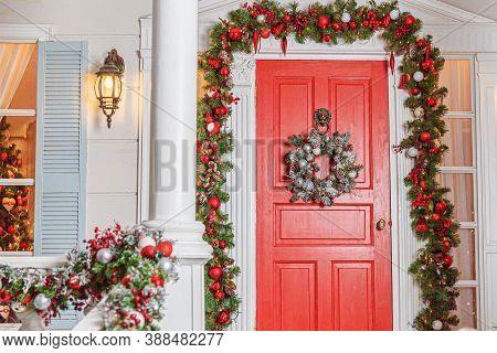 Christmas Porch Decoration Idea. House Entrance With Red Door Decorated For Holidays. Red And Green