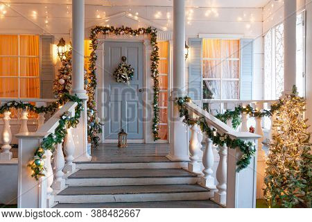 Christmas Porch Decoration Idea. House Entrance Decorated For Holidays. Golden And Green Wreath Garl