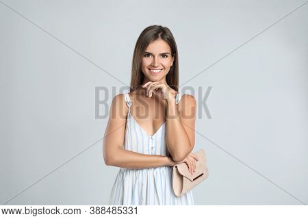 Young Woman Wearing Stylish Dress With Elegant Clutch On Light Grey Background