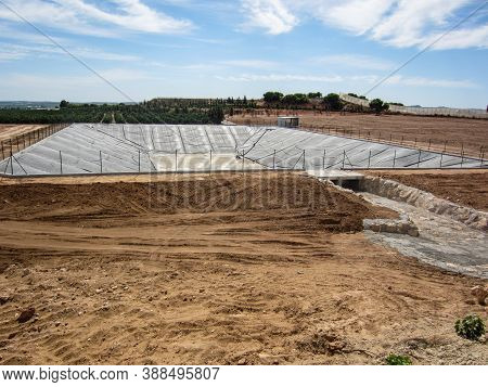 Farm Reservoir For Field Irrigation Under Construction On Spanish Farmland