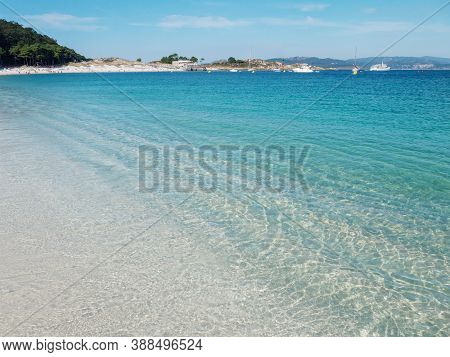 Crystal Clear Blue Sea At The Cies Islands. Turquoise Shallow Water And White Rodas Sandy Beach.