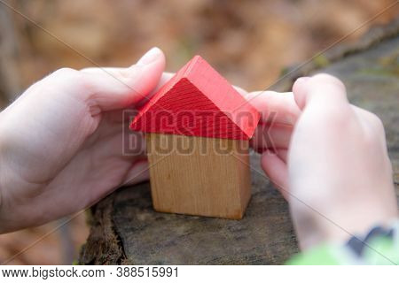 A Small Toy House Made Of Wood With A Red Roof Stands On A Stump In The Open Air. The Symbol Of The