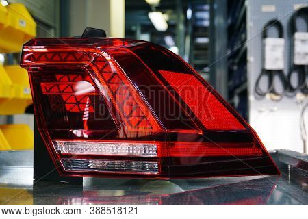 Taillight Of A Modern Car Close Up. In The Background, A Spare Parts Warehouse Is Blurred.