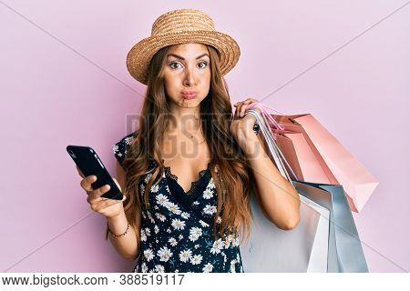 Young brunette woman holding shopping bags and smartphone puffing cheeks with funny face. mouth inflated with air, catching air.