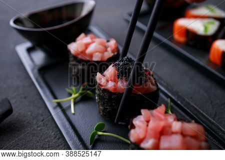 Eating Sushi. Chopsticks Taking Gunkan Maki Sushi From Plate. Japanese Food, Deluxe Restaurant Menu,