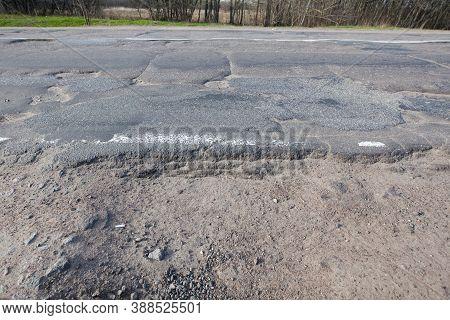 Bad Quality Road With Potholes. Hole In Asphalt. Pit, Unsafe, Hole Road. Transportation, Destruction