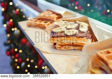 Belgian Waffles Served With Banana And Chocolate Sauce At The Christmas Market Street Food Cafe With