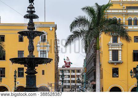 Lima, Peru - December 4, 2008: Red Santa Claus Mascotte On Roof Visible Through Pje De Jose Olaya Al
