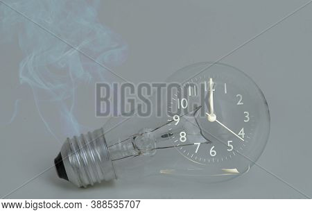 Abstract A Light Bulb With Soot From Working And A Black Analog Clock. Show The Concept Of Saving Re