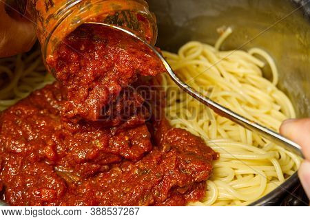 Add Bolognese Sauce On Spaghetti In Pot. Cooking Pasta Bolognese At Home