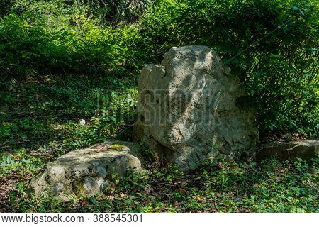 Large Boulder Between Two Smaller Boulders In Shaded Mountainside Park.