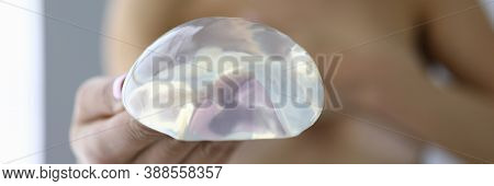 Woman Holds Silicone Breast Implant In Her Hand. Breast Augmentation And Correction Surgery Concept