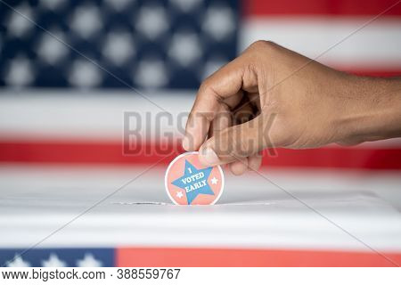 Close Up Of Hands Placing I Voted Early Sticker Inside The Ballot Box - Concept Of Early Voting In U