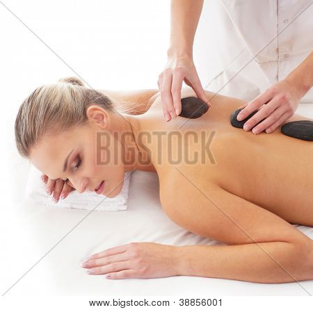 Young attractive woman getting hot stone treatment over white background
