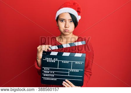 Beautiful young woman with short hair wearing christmas hat holding clapboard puffing cheeks with funny face. mouth inflated with air, catching air.