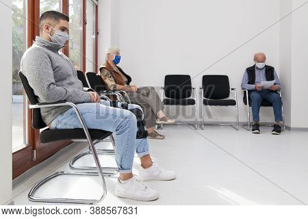 Young And Old People With Face Masks Keeping Social Distance In A Waiting Room Of A Hospital Or Offi