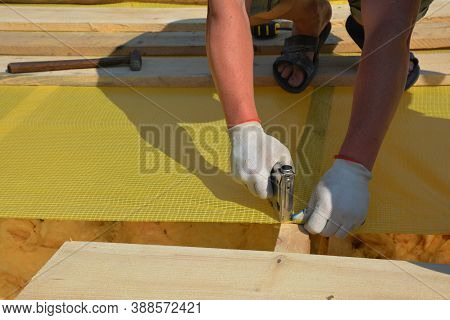 A Building Contractor In Protective Gloves Is Installing Waterproofing Vapor Barrier Using A Staple