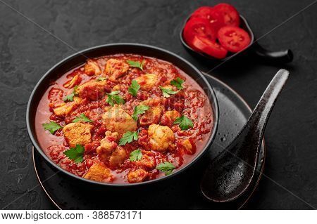 Chicken Madras Curry In Black Bowl On Dark Slate Table Top. Indian Cuisine Dish With With Chicken Me