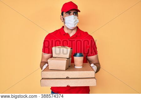 Handsome hispanic man with beard holding delivery food wearing medical mask smiling looking to the side and staring away thinking.