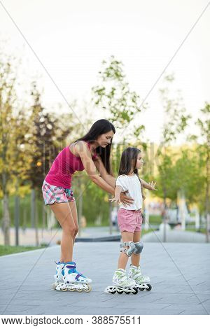 Beautiful Mother And Her Little Daughter Rollerskating In Park