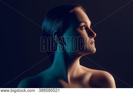 Neon Light Portrait. Female Beauty. Profile Silhouette Of Confident Woman With Bare Shoulders In Blu