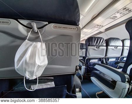 Protective Medical White Safety Mask Hanging In Airplane For Covid-19, Travel And Coronavirus Concep