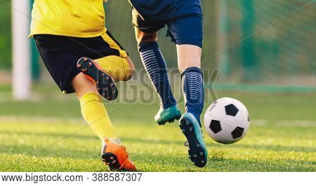 Close-up Of Two Youth Footballers Running In A Duel. Soccer Players In Football Cleats