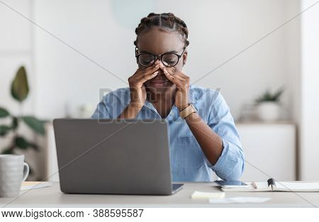 Eye Strain. Tired African American Female Office Worker Sitting At Workplace Massaging Nosebridge, W