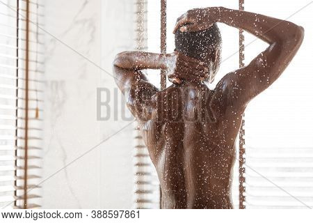 Unrecognizable African American Man Taking Shower Washing Body Standing Back To Camera Under Falling