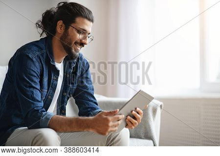 Millennial Western Guy Spending Time With Digital Tablet At Home, Reading News, Browsing Internet, W