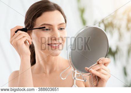 Smiling Young Woman Looking At Hand Mirror, Applying Mascara, Home Interior, Copy Space. Cheerful At