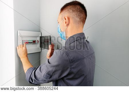 an electrician repairing a mask switch during a pandemic covid - 19. Hands of electrician with electric actuator equipment in fuse box