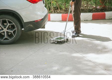 Security Guard Checking Car Floor With Inspection Mirror For Threats Of Bomb. Inspection Mirror For