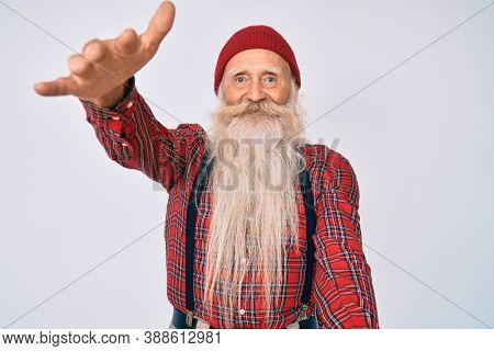 Old senior man with grey hair and long beard wearing hipster look with wool cap looking at the camera smiling with open arms for hug. cheerful expression embracing happiness.