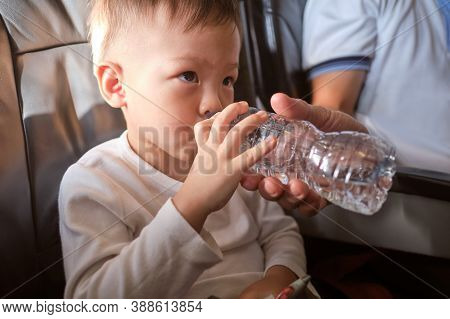 Cute Little Asian 3 Years Old Toddler Boy Child Drinking Water From Bottle During Flight On Airplane