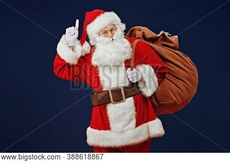 Attention, Christmas! Santa Claus raises his index finger to attract attention. Studio portrait over dark blue background.