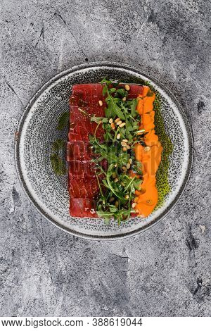 Beef Carpaccio With Arugula And Pine Nuts Cold Appetizer On A Gray Plate.