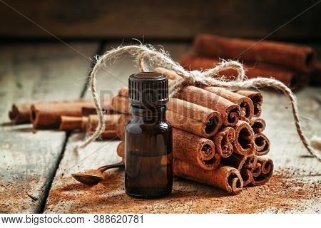 Essential Cinnamon Oil In A Small Bottle, Ground Cinnamon And Cinnamon Sticks On Old Wooden Backgrou