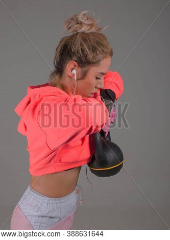 Fitness Lady Makes Cross Training With Kettlebell, Gray Background
