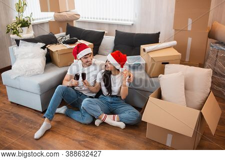 Newlywed Couple Celebrate Christmas Or New Year In Their New Apartment. Young Happy Man And Woman Dr